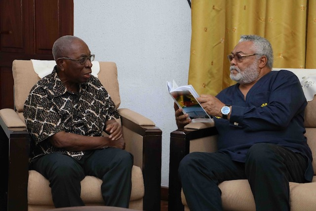 Rawlings taking a look at the book presented by Samuel Ntim Darkwa