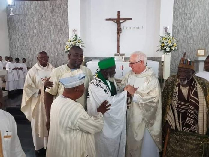 The chief imam Sheikh Sharubutu (in green scarf) and Father Campbell at the Christ the King Church in Accra