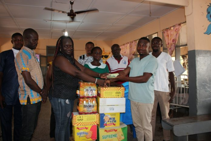 Ophelia Aovare presenting the items to the Nurse In-Charge, Adongo Joshua.