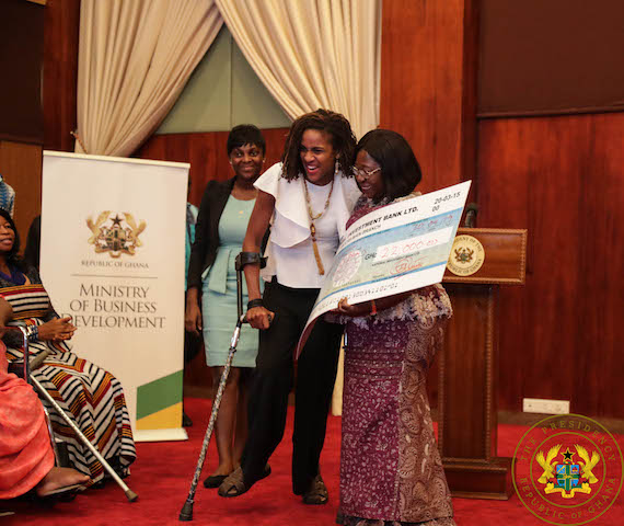 Chief of Staff, Akosua Frema Opare Osei presenting a cheque to one of the beneficiaries