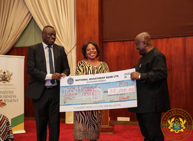 President Akufo-Addo presenting a cheque to one of the beneficiaries