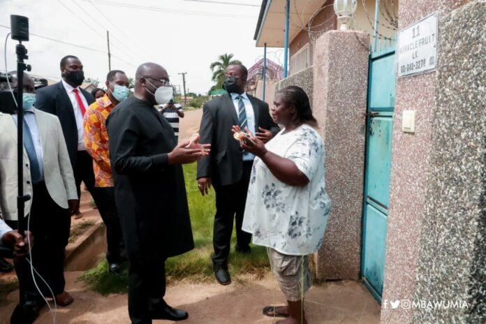 Dr Mahamudu Bawumia interacting with a house owner during the digital address system installation