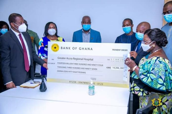 Chief of Staff Frema Osei-Opare presenting the cheque for the surgery of the conjoined twins