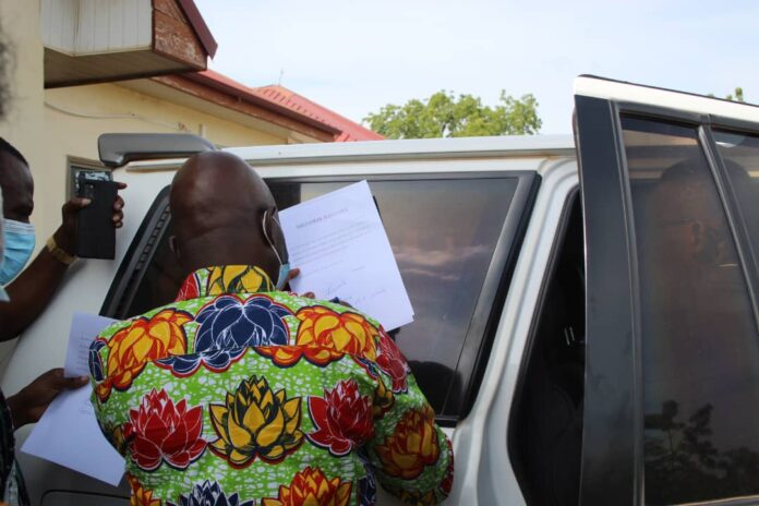 The Upper East Regional Minister, Stephen Yakubu, appending his signature to the oath after the DCE nominee, Agnes Namoo, was sworn in inside a car on Sunday.